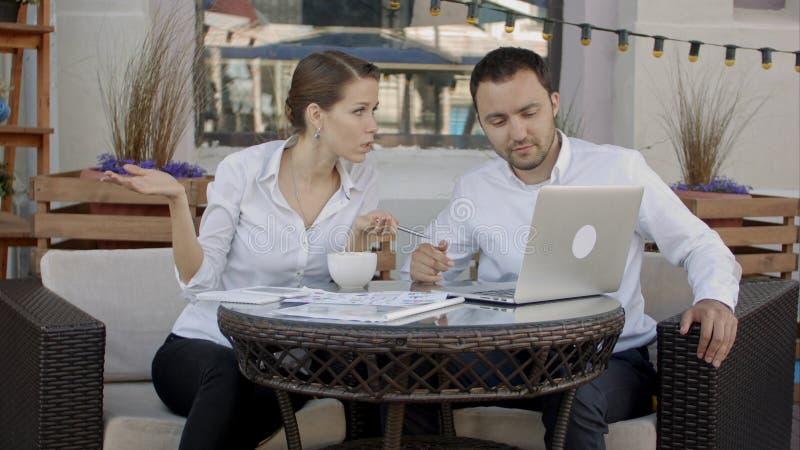 买卖人与在咖啡馆的便携式计算机一起使用 事务、技术和人们 库存图片