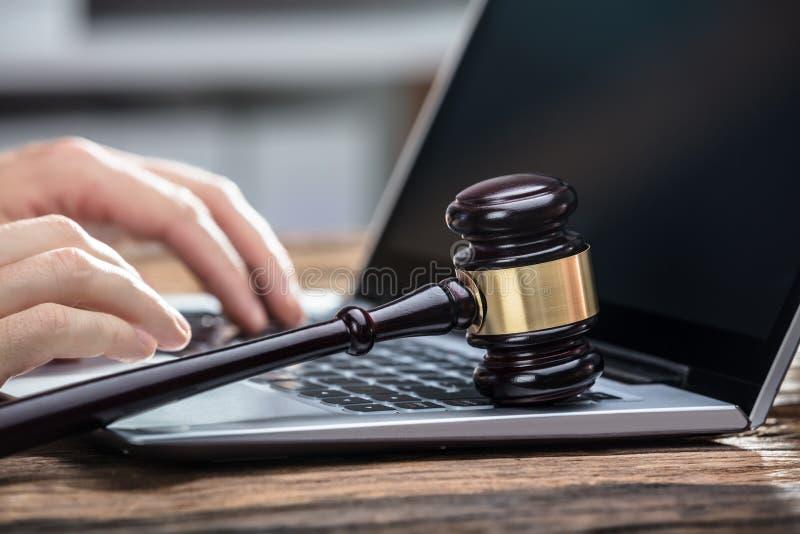买卖人使用膝上型计算机的` s手在木书桌上 免版税库存照片