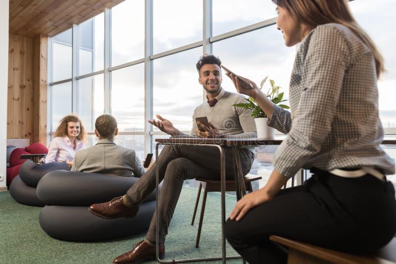 买卖人在Coworking中心,工友工作场所混合种族人见面编组 库存图片