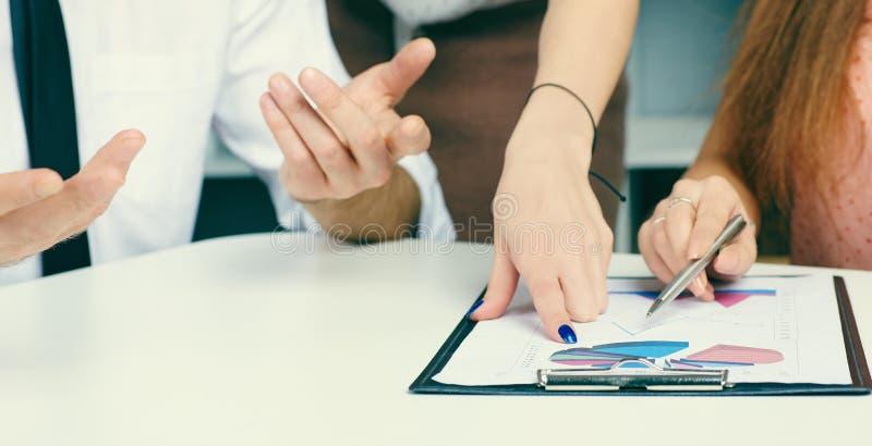 买卖人有关于财政报告的一次讨论在办公室 免版税库存照片