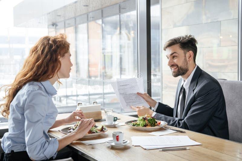 买卖人有工作午餐在坐在窗口附近的餐馆吃谈论的沙拉快乐的项目 免版税库存照片