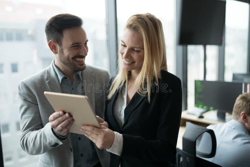 买卖人谈论,当使用数字片剂在办公室时 免版税库存图片