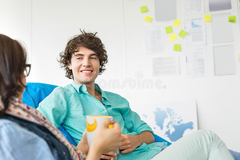 买卖人食用咖啡,当放松在装豆子小布袋椅子在创造性的办公室时 库存照片