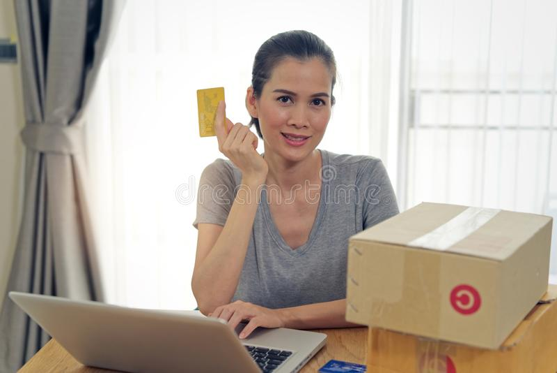 买在网上从网站的亚裔美女使用付款的信用卡 免版税图库摄影