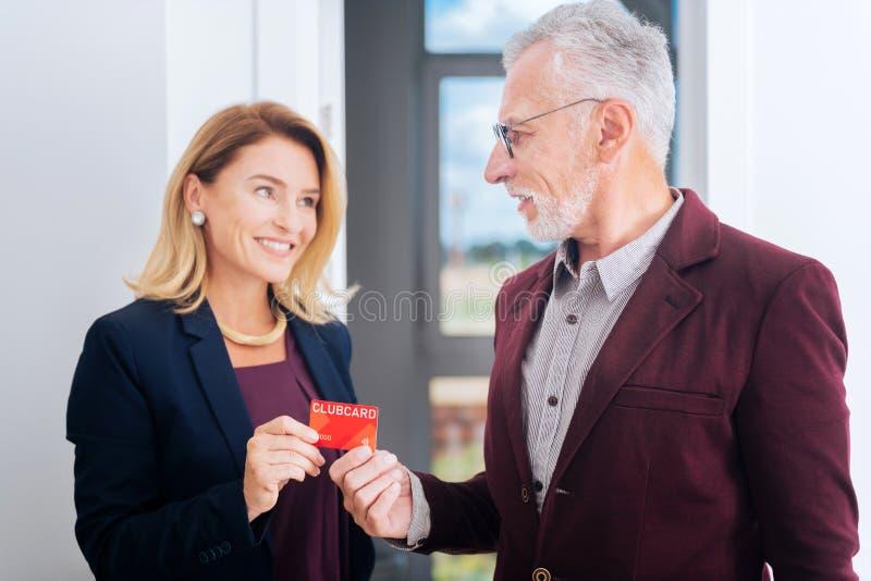 买新房的有胡子的商人给他的信用卡房地产经纪商 库存图片