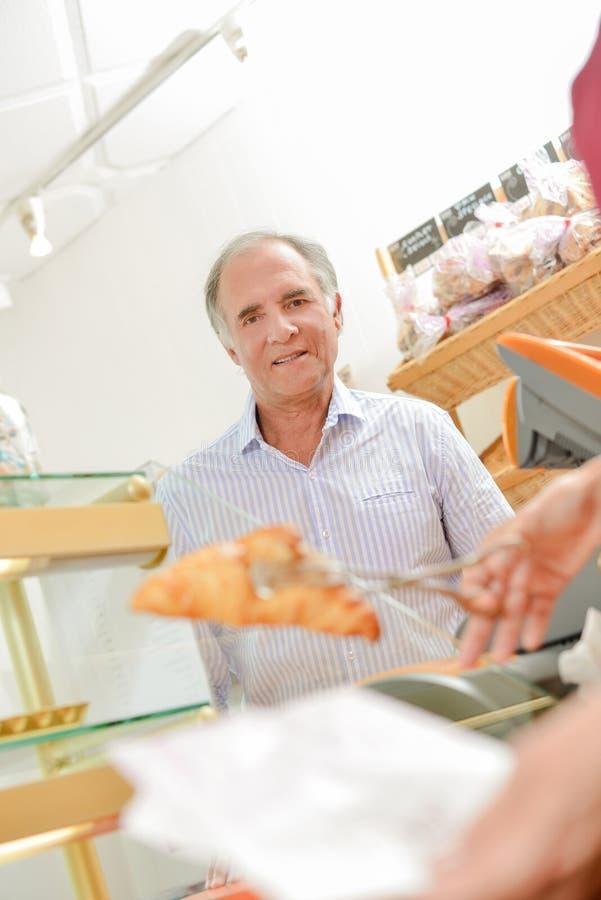 买新月形面包的顾客 免版税库存照片