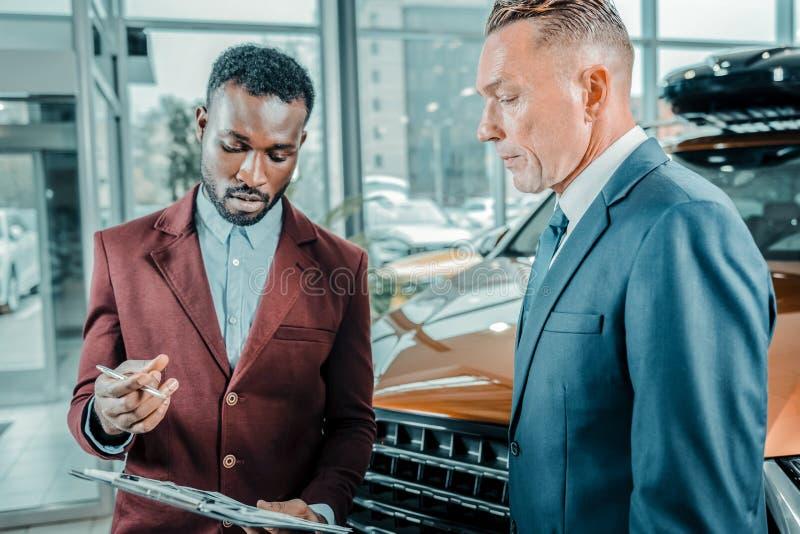 买新的汽车的严肃的商人在汽车陈列室里 免版税库存照片