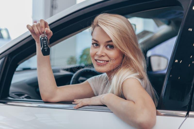 买新的汽车的美丽的年轻女人在经销权 免版税库存图片