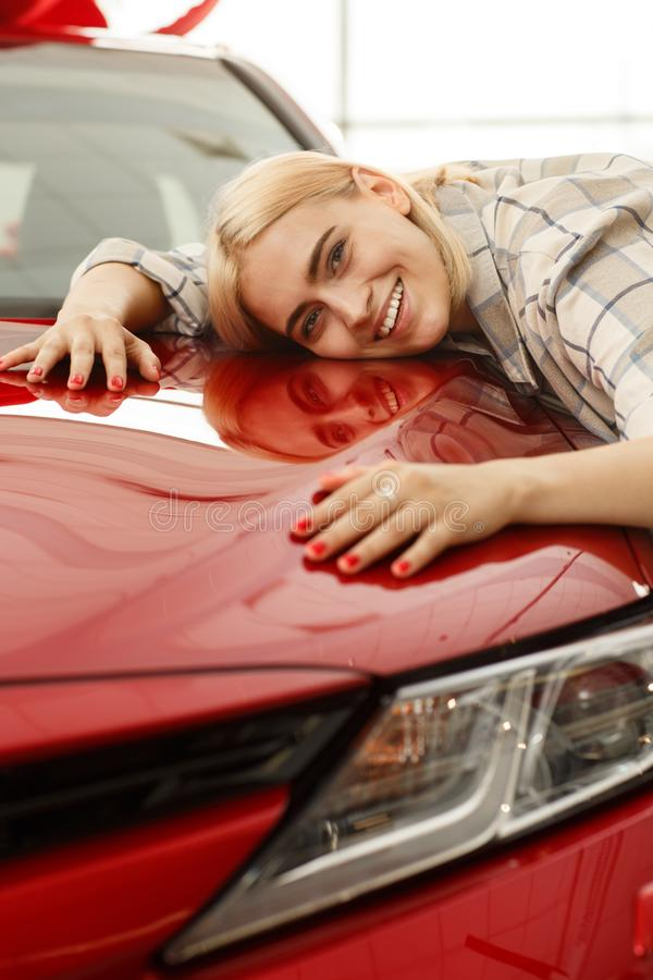 买新的汽车的美丽的年轻女人在经销权 库存照片