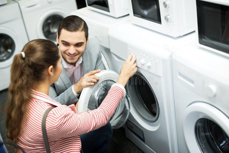 买新的衣裳洗衣机的愉快的家庭夫妇 图库摄影