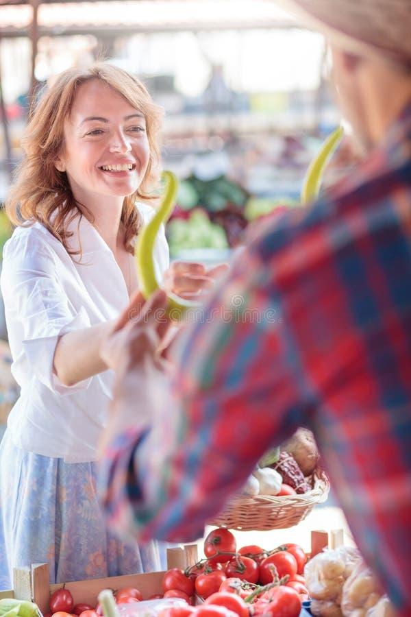 买新鲜的有机蔬菜的愉快的微笑的中间妇女在一个露天市场 库存照片