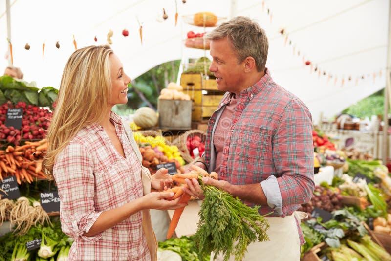 买新鲜蔬菜的妇女在农夫市场摊位 免版税库存照片
