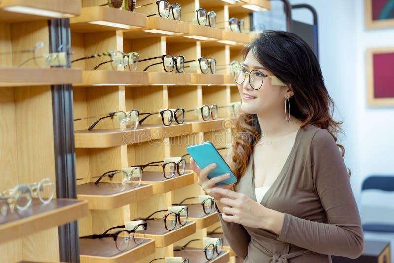 买的网上玻璃美丽的年轻亚洲妇女藏品智能手机 免版税图库摄影