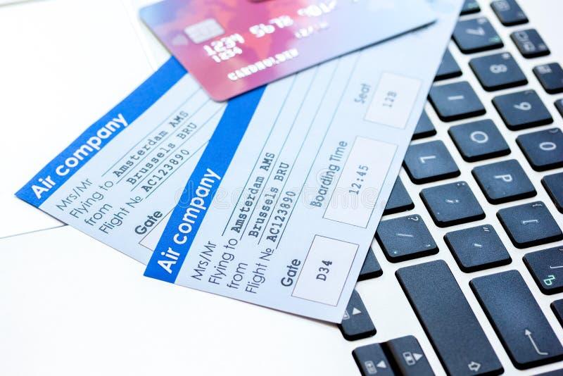 买的飞机票在网上与在键盘背景的信用卡 免版税库存照片
