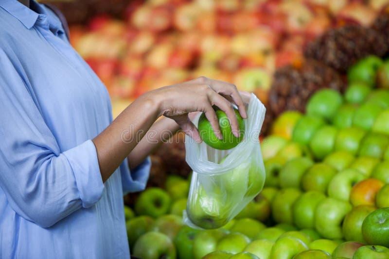买苹果的妇女 免版税库存照片