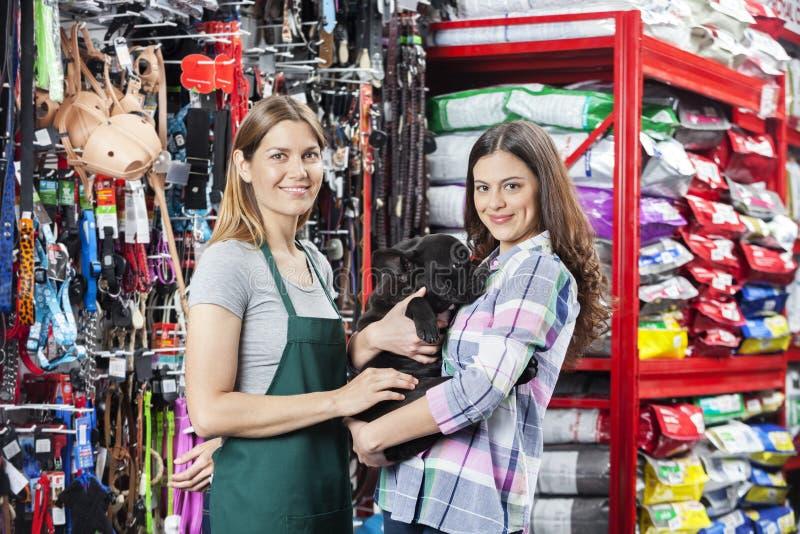 买从女推销员的愉快的妇女法国牛头犬在商店 免版税库存照片