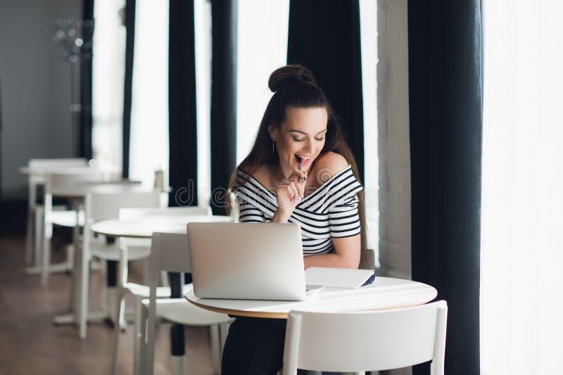 乱动笔和认为在主题的俏丽的妇女照片,当坐在与她的膝上型计算机时的某一咖啡店 免版税库存图片