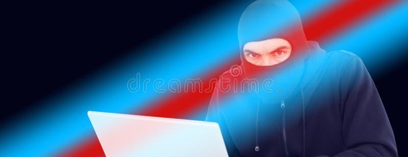 乱砍膝上型计算机的巴拉克拉法帽的黑客 库存照片