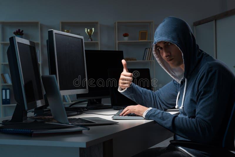乱砍计算机的黑客在晚上 免版税库存照片