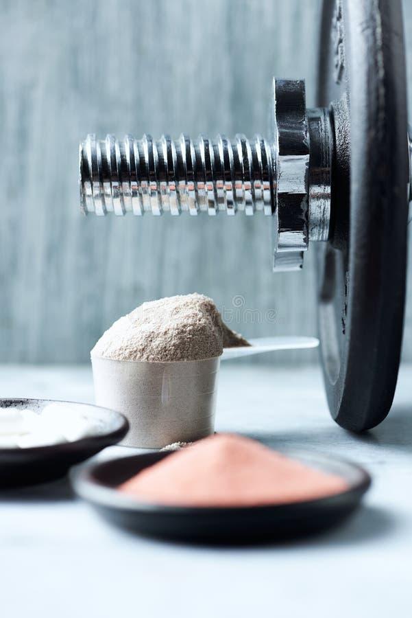 乳清蛋白、Beta胺基代丙酸胶囊、肌酸粉末和一个哑铃瓢在背景中 免版税库存图片