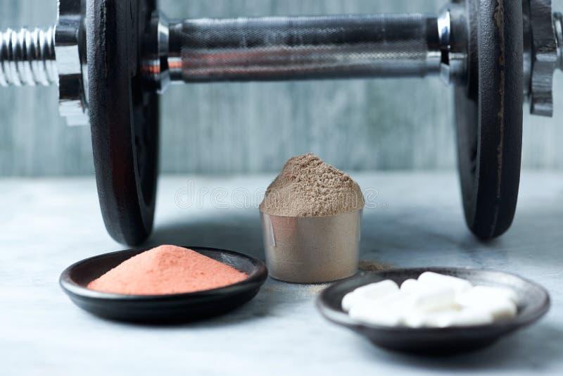 乳清蛋白、Beta胺基代丙酸胶囊、肌酸粉末和一个哑铃瓢在背景中 库存照片
