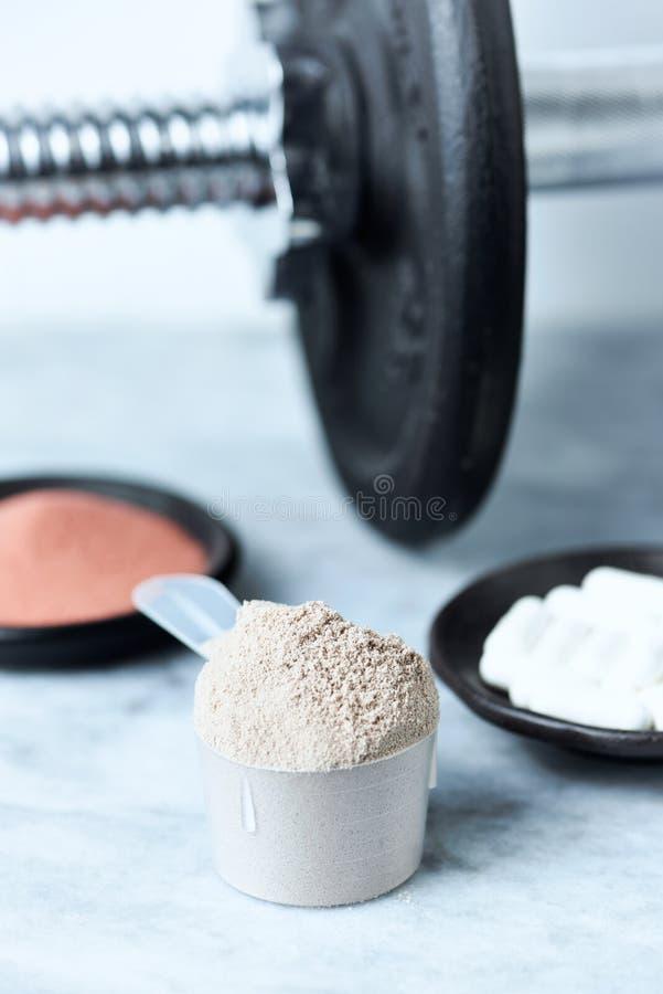 乳清蛋白、Beta胺基代丙酸胶囊、肌酸粉末和一个哑铃瓢在背景中 库存图片