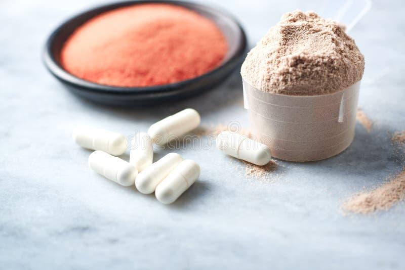 乳清蛋白、Beta胺基代丙酸胶囊和肌酸粉末瓢  体育营养 免版税库存图片