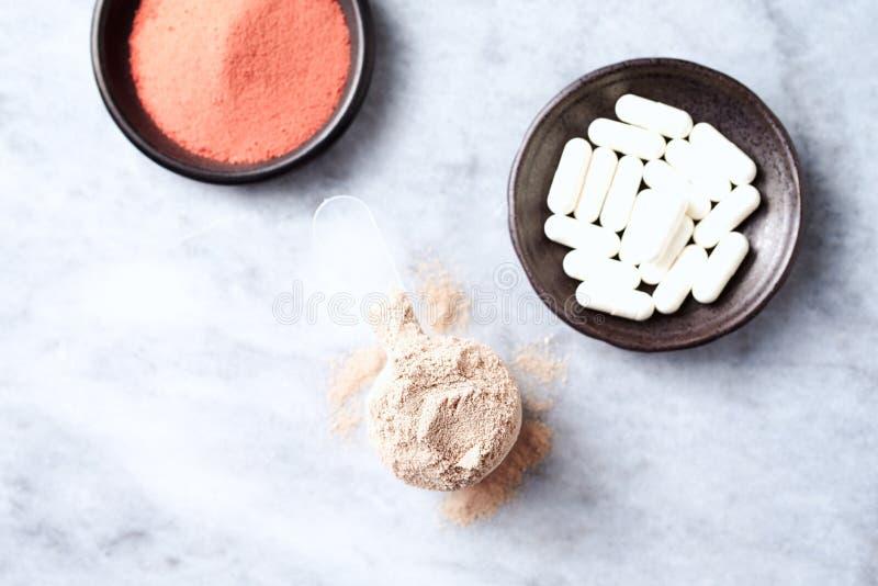 乳清蛋白、Beta胺基代丙酸胶囊和肌酸粉末瓢  体育营养 库存照片