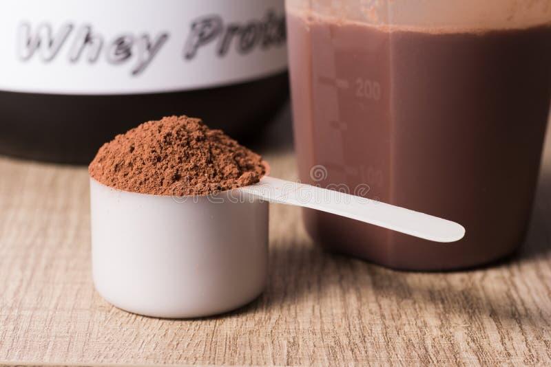 乳清蛋白 有巧克力味道粉末的,振动器白色瓢 免版税库存照片