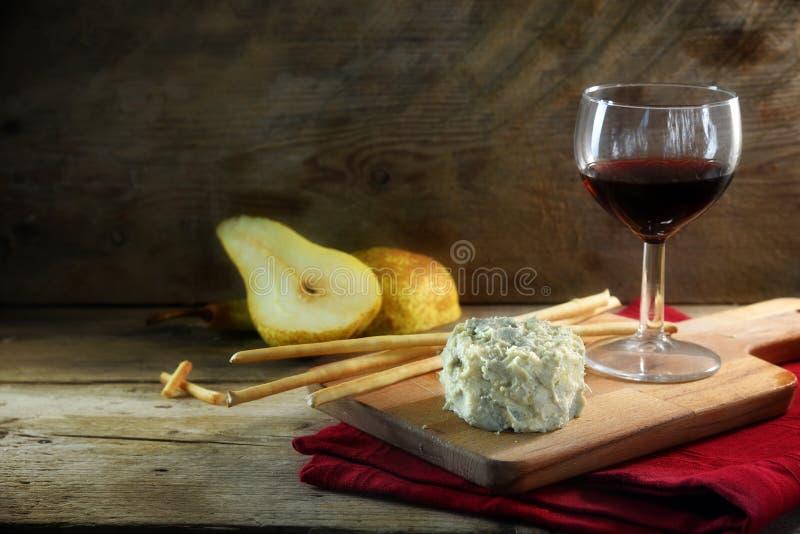 乳脂状的蓝色stilton乳酪、葡萄酒、梨和一些薄脆饼干st 库存照片