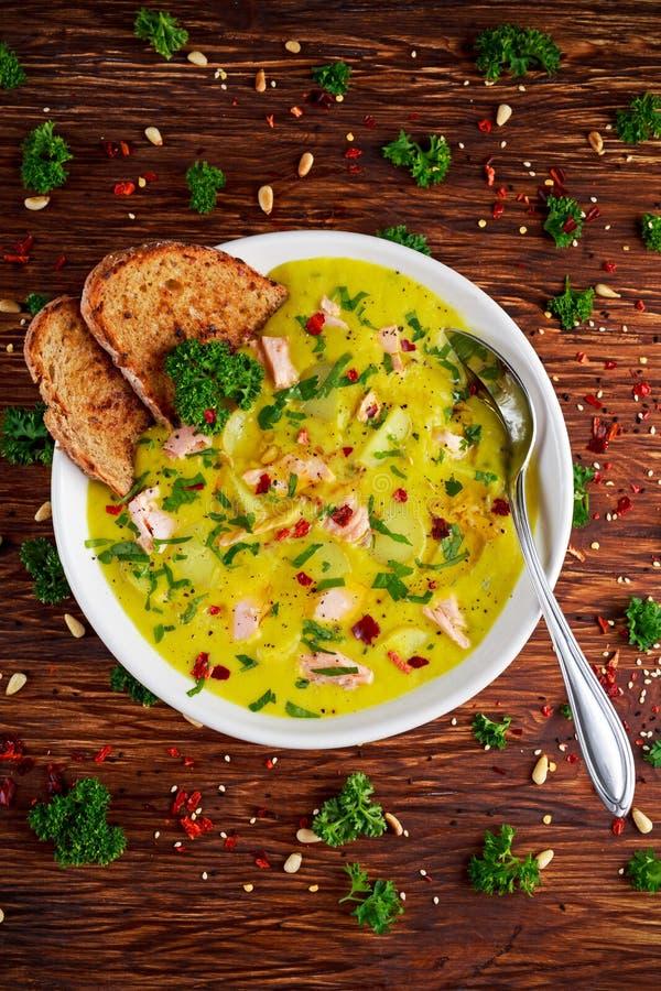 乳脂状的鱼三文鱼,韭葱,在木背景的土豆汤 免版税库存照片