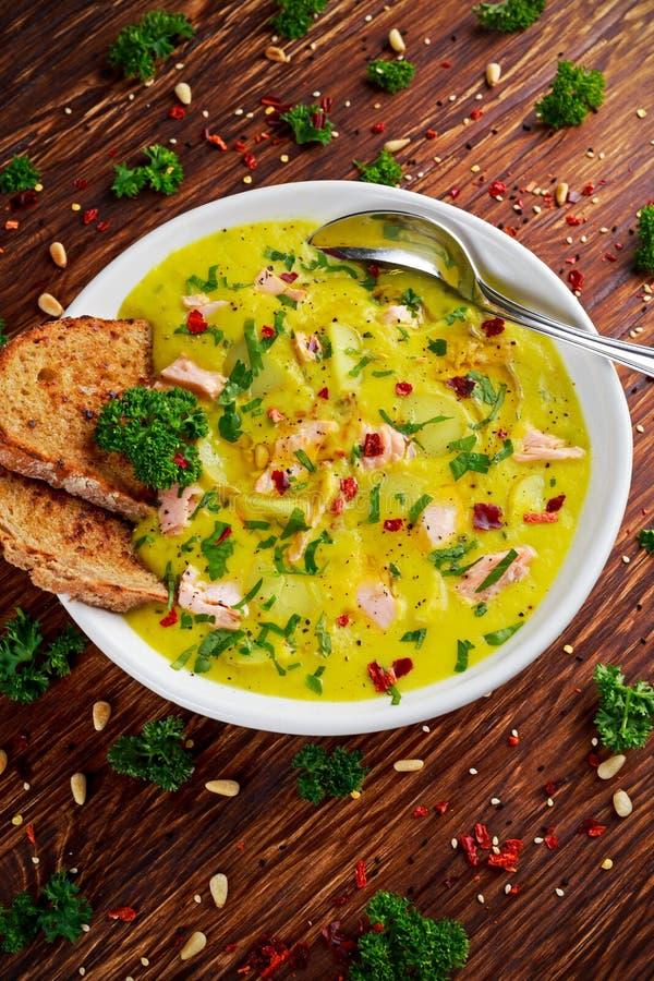 乳脂状的鱼三文鱼,韭葱,在木背景的土豆汤 免版税库存图片