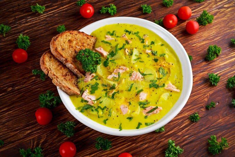 乳脂状的鱼三文鱼,韭葱,在木背景的土豆汤 库存照片