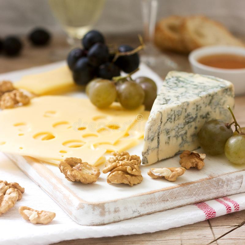 乳酪、葡萄、坚果和蜂蜜的各种各样的类型开胃菜,供食与白色和红酒 土气样式 免版税库存照片