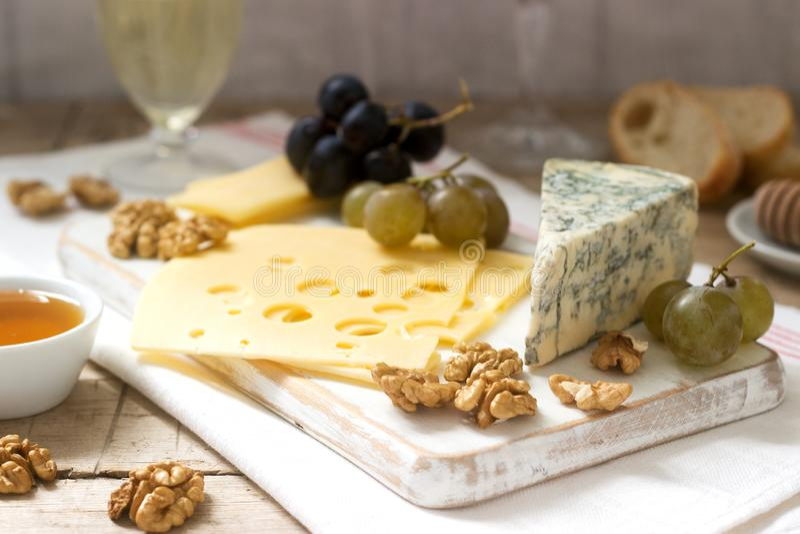 乳酪、葡萄、坚果和蜂蜜的各种各样的类型开胃菜,供食与白色和红酒 土气样式 免版税图库摄影