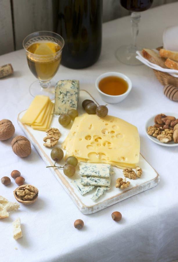 乳酪、葡萄、坚果和蜂蜜的各种各样的类型开胃菜,供食与白色和红酒 土气样式 免版税库存图片