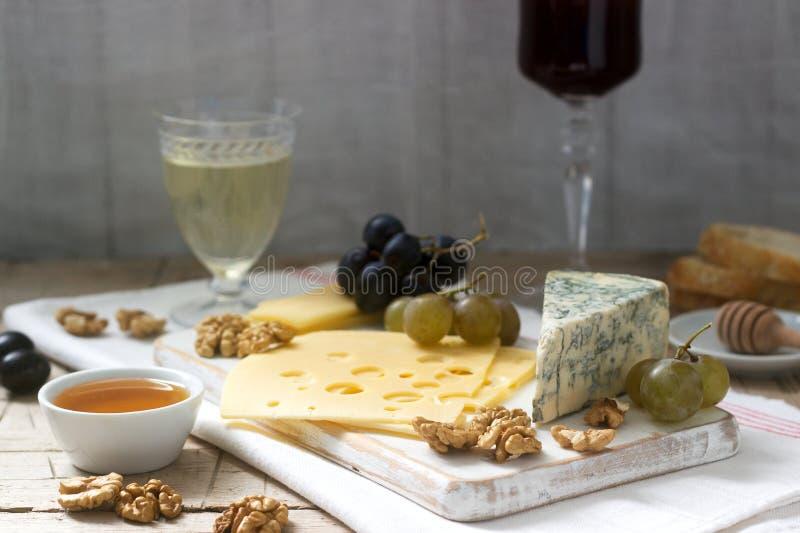乳酪、葡萄、坚果和蜂蜜的各种各样的类型开胃菜,供食与白色和红酒 土气样式 库存照片