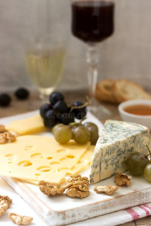 乳酪、葡萄、坚果和蜂蜜的各种各样的类型开胃菜,供食与白色和红酒 土气样式 图库摄影