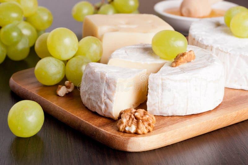 乳酪、葡萄和核桃在木背景,水平 免版税库存照片