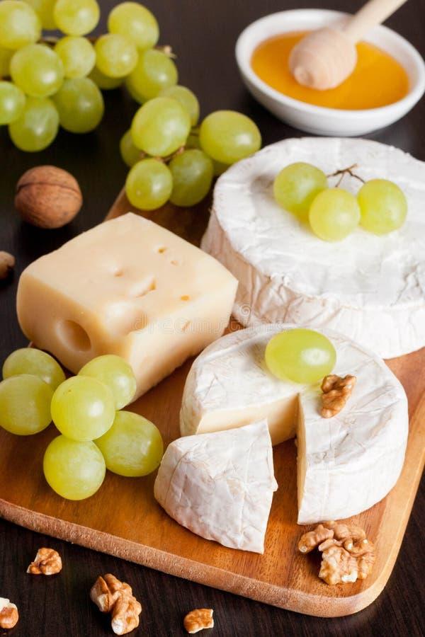 乳酪、蜂蜜、葡萄和核桃在木背景 库存照片