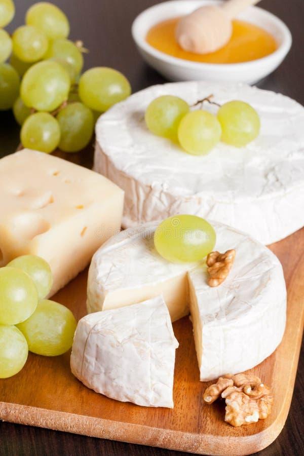 乳酪、蜂蜜、葡萄和核桃在木背景 免版税库存图片