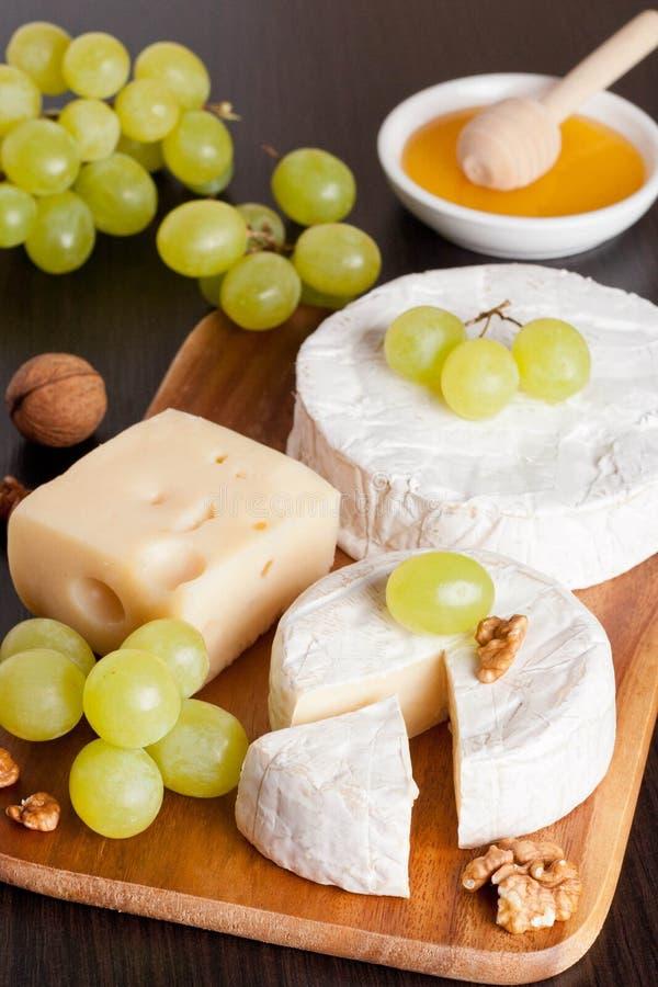 乳酪、蜂蜜、葡萄和核桃在木背景 免版税库存照片