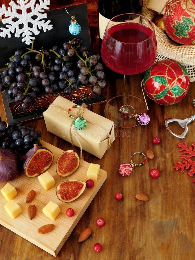 乳酪和无花果在一个木板、红葡萄酒在玻璃,葡萄和圣诞节属性 库存照片