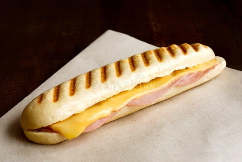 乳酪和火腿敬酒了panini 在包装纸和木头 库存照片