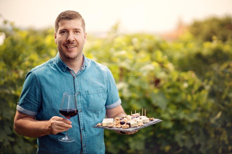 乳酪和葡萄英俊的年轻人藏品葡萄酒杯和板材画象在葡萄园 酿酒商欢迎游人在 免版税图库摄影