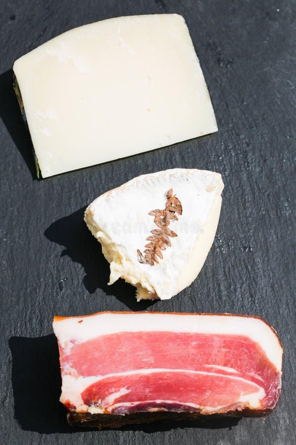 乳酪和Tyrolean烟肉在板岩,pecorino,法国软干酪 库存图片