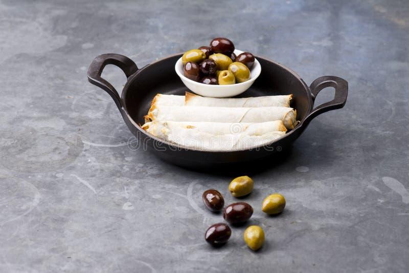 乳酪在土气背景滚动板材用在一个黑平底锅供食的橄榄 库存图片