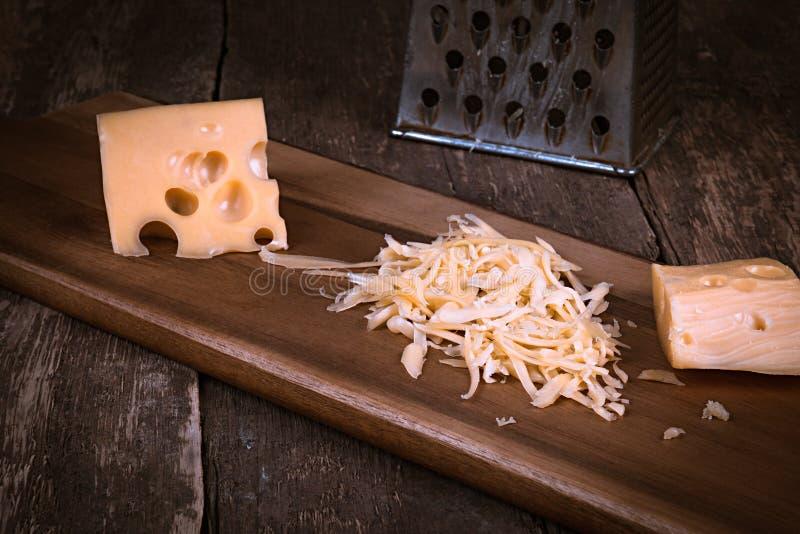 乳酪在片断和磨碎和在一个木切板的一台使用的金属磨丝器反对与拷贝空间的黑暗的板岩背景 免版税库存图片