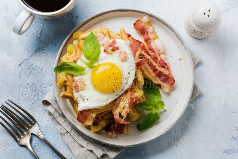 乳酪奶蛋烘饼用油煎的烟肉、鸡蛋和帕尔马干酪用香料和蓬蒿早餐在轻的老具体背景 免版税图库摄影