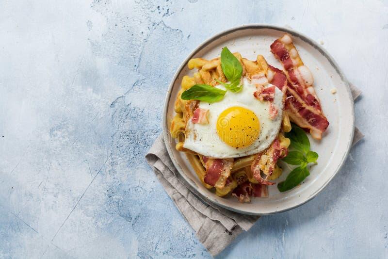 乳酪奶蛋烘饼用油煎的烟肉、鸡蛋和帕尔马干酪用香料和蓬蒿早餐在轻的老具体背景 免版税库存图片